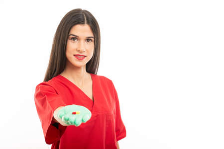 Selective focus of beautiful nurse wearing scrubs showing one pill isolated on white background Фото со стока