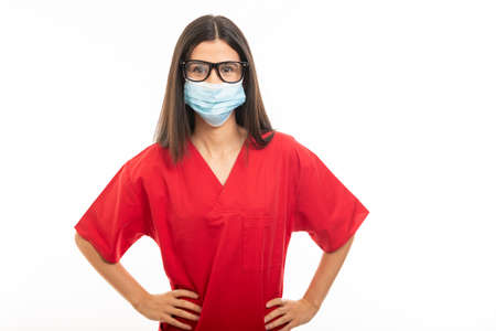 Portrait of beautiful young nurse wearing scrubs and face sterile mask isolated on white background with copy space advertising area