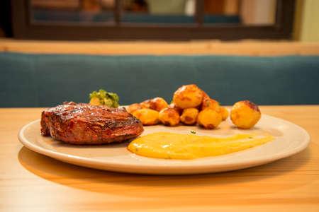 Tasty beef steak with potato and sauce on bistro or restaurant table Reklamní fotografie