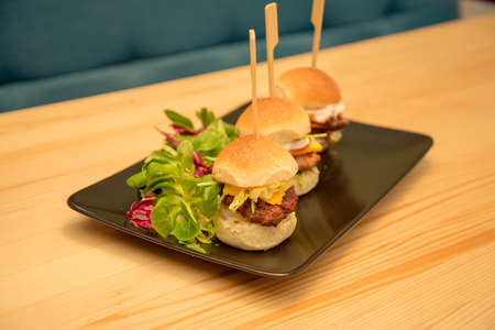 Tasty mini burgers with salad on bistro wooden table