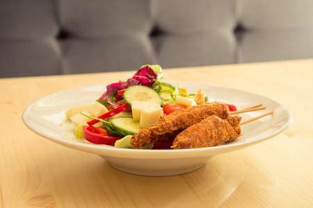 Tasty salad with chicken cheese and raw vegetables on bistro or restaurant wooden table