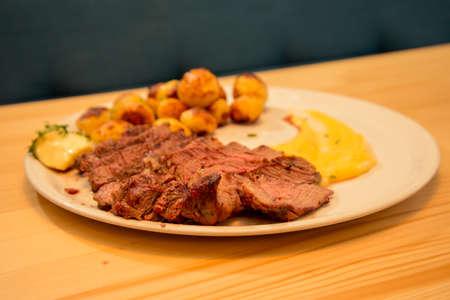 Sliced tasty beef steak with potato and sauce on bistro or restaurant table Reklamní fotografie