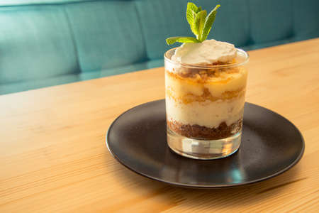 Tasty tiramisu on glass with mint on bistro table with copy space advertising area