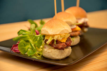 Close-up tasty mini burgers with salad on bistro table