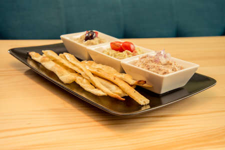 Tasty bread sticks with bunch of dips on bistro plate