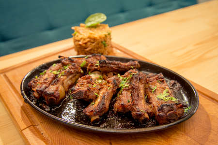 Tasty ribs with garnish on pub or bistro table