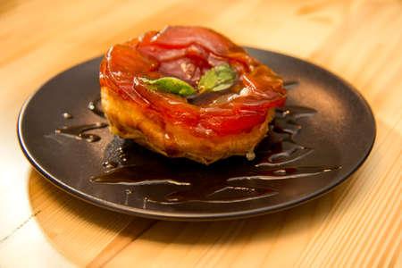 Sticky tasty apple caramelized desert on restaurant or bistro table