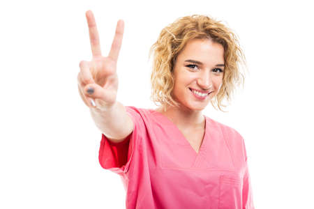 Portrait of young nurse wearing pink scrub showing peace gesture isolated on white background with copy space advertising area
