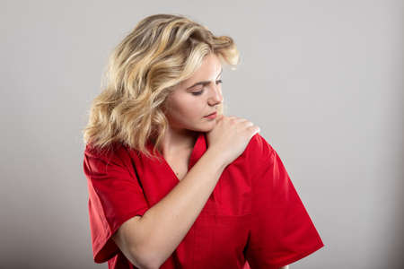 Portrait of female nurse wearing red scrub holding shoulder like hurting on studio gray background with copy space advertising area