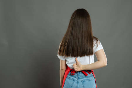 Back view of female supermarket employee holding lower back like hurting on gray background with copy space advertising area Stock Photo