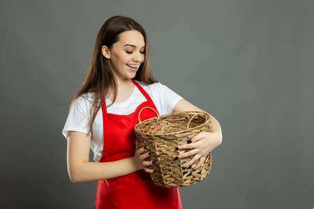 Portrait of young female supermarket employee holding empty pockets on gray background with copy space advertising area