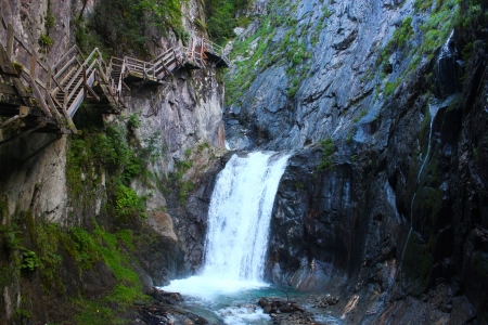 cliffside hiking steps near waterfall in switzerland photo