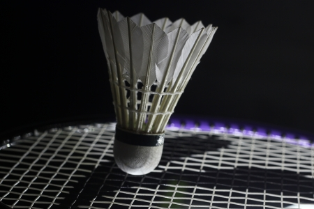 sidelit: side-lit tennis racket hitting shuttlecock in the tip