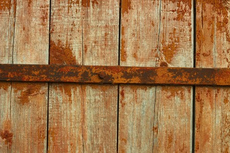depraved: Old wooden door with rusted metal bar Stock Photo
