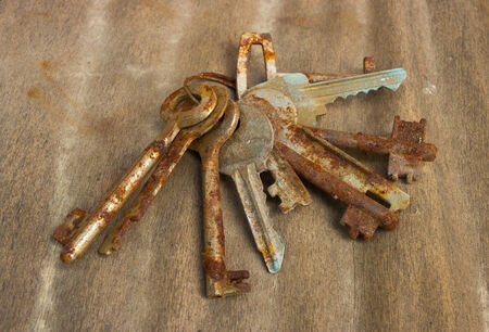 Old and rusty ring of keys on wood photo