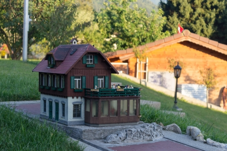 Miniature wooden house model in front yard photo