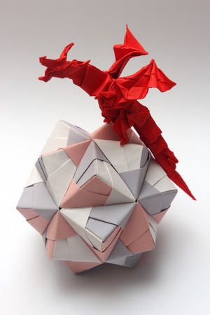 Vibrant red origami dragon conquering colorful origami ball photo