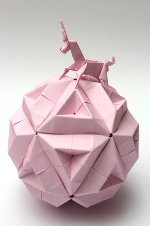 Pink origami unicorn riding modular origami ball isolated on white photo