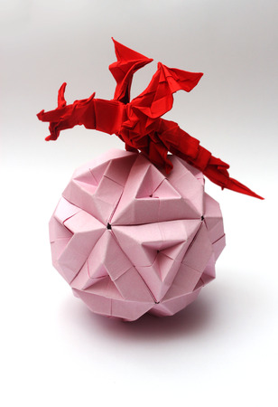 Red origami dragon conquering pink paper ball photo