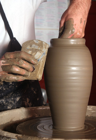 Potters hands making traditional jar on pottery wheel  photo