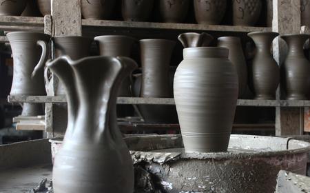 Unfinished ceramic vase on wheel in pottery workshop photo