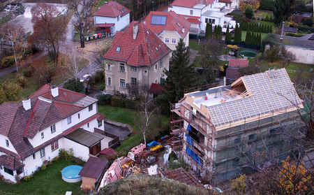 Aerial shot of a new house being built in a suburban historic neighborhood near a waterfall  in autumn photo