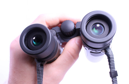 POV Hand holding pair of binoculars isolated on white background photo