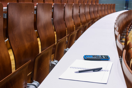 science background: notebook, pen and calculator in empty university lecture room