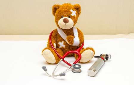 Brown teddy bear with bandages and broken hand in pediatricians office