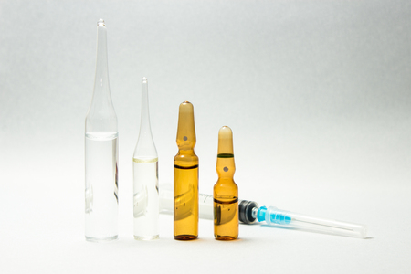 Syringe and group of ampules sorted by size isolated on white background