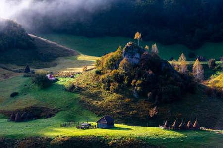 Vista mozzafiato sul remoto villaggio coperto di nebbia all'ora d'oro, Fundatura Ponorului, contea di Hunedoara, Romania Archivio Fotografico