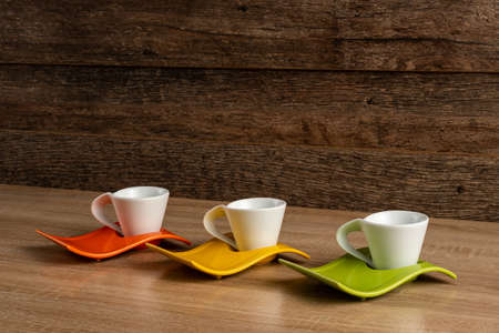 Side left to right inclined view of white coffee cups place on three colours plates.