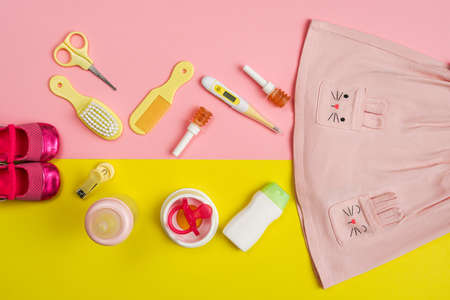 Newborn care essentials with baby girl shoes, top view