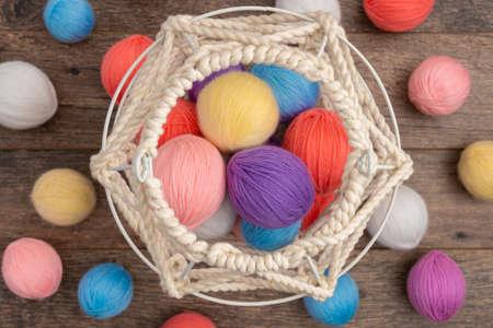 Colorful yarn balls and white knit basket Standard-Bild