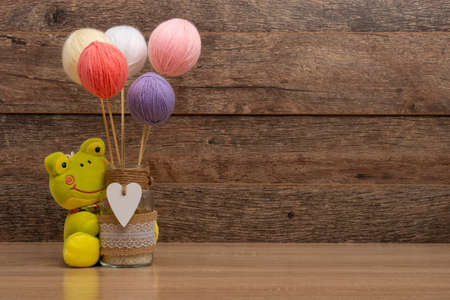 Pastel color thread balls and jars on wooden background
