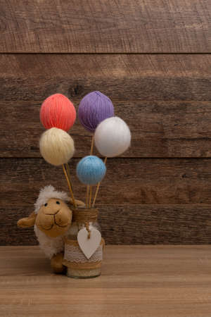 Baby stuffed sheep and colored wool balls, top view
