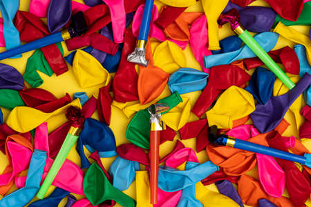 Party whistles and deflated balloons, flat lay. Colored party whistles and colorful deflated balloons on yellow background, top view. Stock photo for ads and party invites.