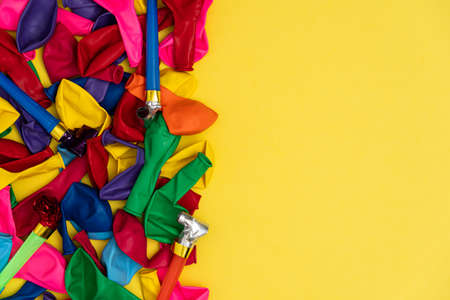 Deflated balloons and whistles, with copy space. Mix of colored balloons and party whistles on yellow background, with right copy space, top view. Perfect template for social media event and birthday