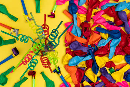 Colored spiral straws and party accessories, flat lay. Spiral straws, deflated balloons and party whistles on yellow background, top view. Stock image for social media events, store sales and party in 写真素材
