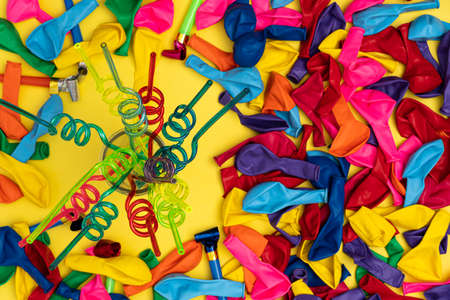 Birthday party whistles, balloons and spiral straws. Top view of colored spiral straws, multicolored balloons and whistles on yellow background, flat lay. Perfect template for Facebook event invitatio 写真素材