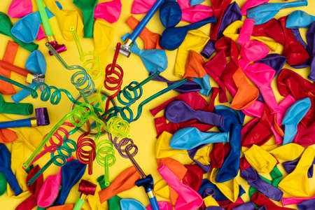 Spiral straws on mason jar and other party essentials. Mason jar with colorful spiral straws, deflated balloons and party whistles on top and view. Perfect for birthday sales, shop anniversary promoti