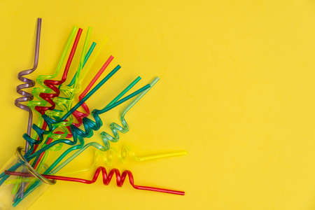 Mixed colors of spiral straws on yellow background. Purple, baby blue and yellow green spiral straws on top view with small copyspace on right. Perfect for custom text and logos. 写真素材
