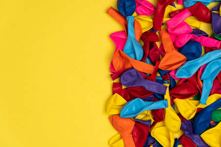Close up view of colored deflated balloons. Top view of colored balloons on yellow background, with left copy space, flat lay. Great for birthday store sales and promotions.