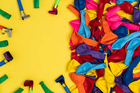 Party accessories on yellow background, flat lay. Multicolor whistles and deflated balloons on yellow background, with copy space, top view. Perfect template for store sales and promotions.