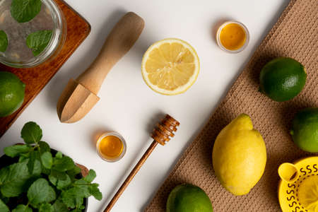 Lemon cutted in half with citrus juicer and mint Standard-Bild - 129463595