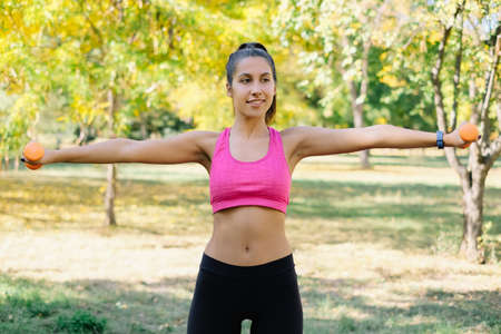 Arms workout with orange dumbbells in park