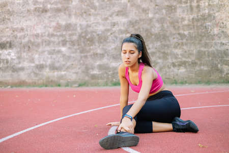 Athletic woman touching her sprained ankle during workout