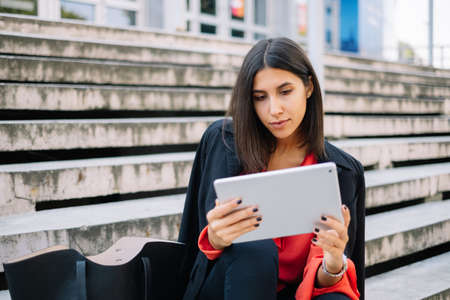 Woman with black bag looking at tablet Imagens