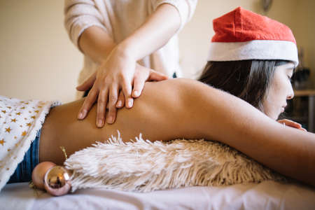 Young woman having massage at beauty SPA salon. Masseuse hands massaging woman's back in massage table with tree balls, with copyspace, close-up. Ideal for blogs, websites and magazines.