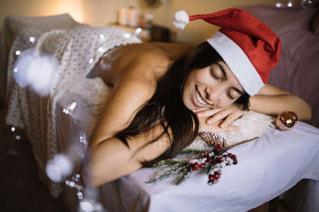 Smiling woman relax on massage table with Christmas decor